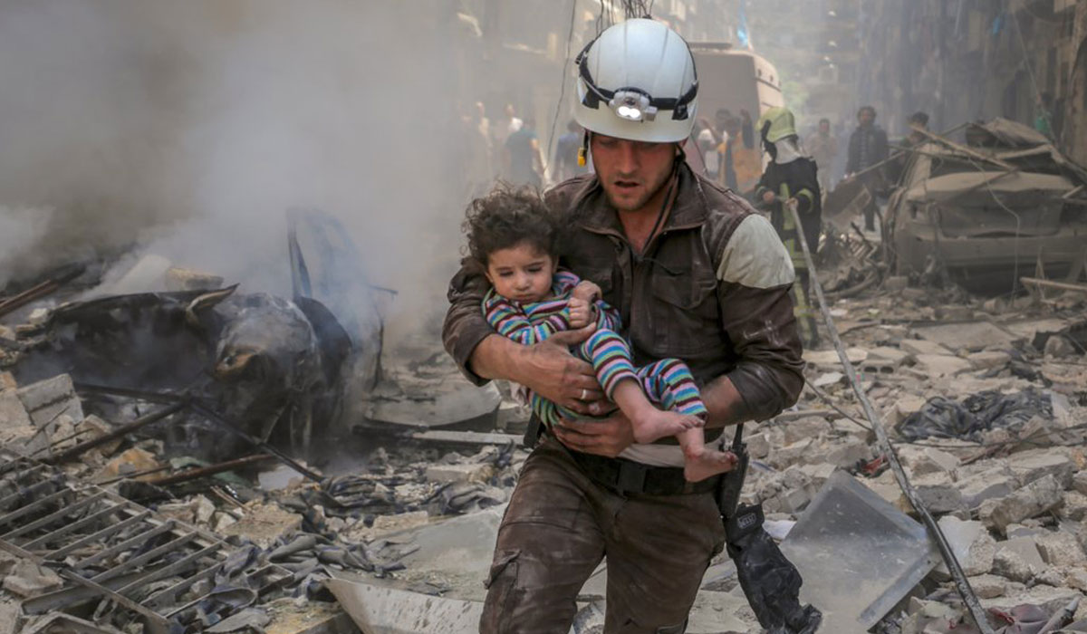One of the 2.900 White Helmets volunteers, who is rescuing a child from a destroyed building, they have saved more than 70.000 lives
